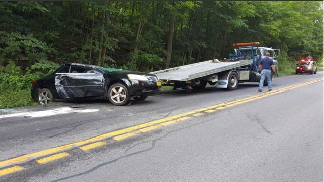 Woman extricated from rolled over car, sustains minor injuries